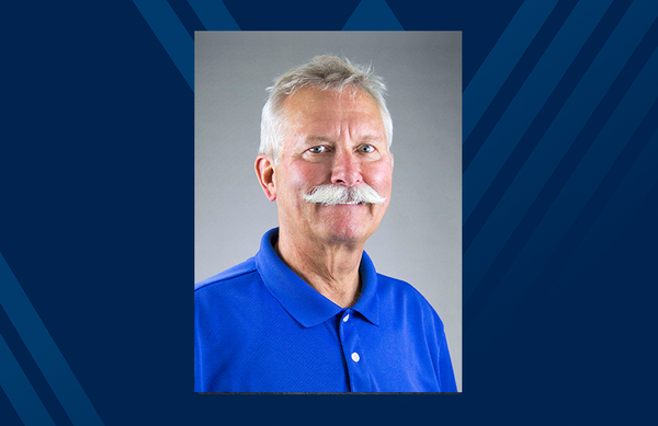 Man in blue shirt and white mustache poses for a headshot